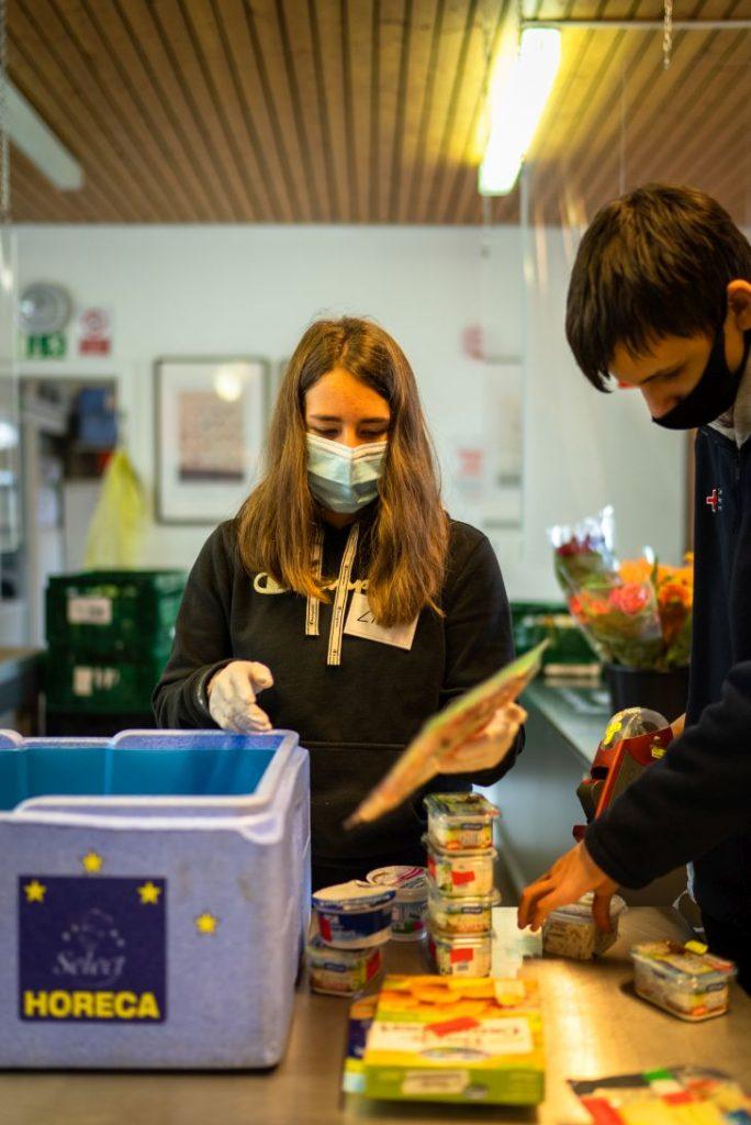 Zwei junge Tafel-Aktive unterstützen die Tafel in Ulm und sortieren Lebensmittel für die Ausgabe.