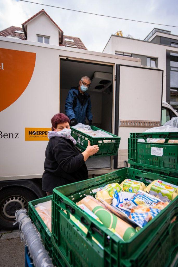 Zwei Tafel-Aktive laden gespendete Lebensmittel vor der Tafel in Ulm aus.