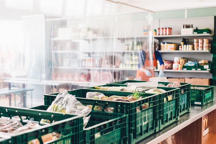 Lebensmittelkisten stehen hinter einer Trennwand, eine Tafel-Mitarbeiterin sortiert Lebensmittel